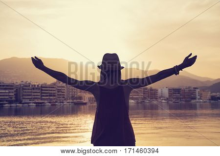 Girl with arms wide open enjoying the sunset / sunrise in bay.