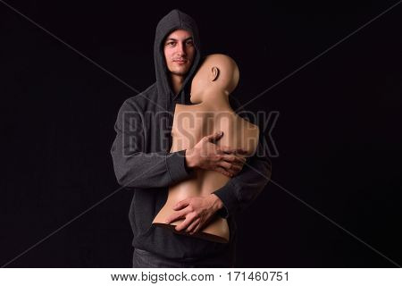 Serious Man Dressed In Black Hoodie Holding In His Arms A Plastic Women Body Mannequin Figure On Dar
