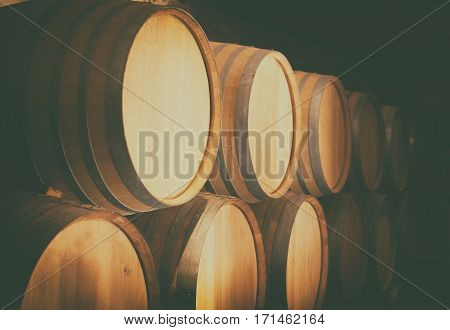Wooden wine barrels stacked in the cellar.