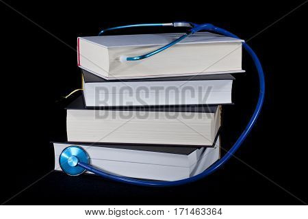 Pile of books on a black background. Stethoscope on top the stack.