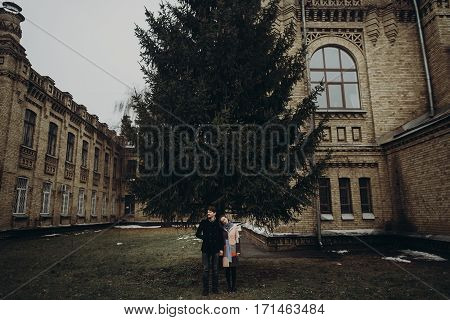 Stylish Man And Woman Posing Under Tree. Romantic Calm Atmospheric Moment. Couple Hugging Gently In