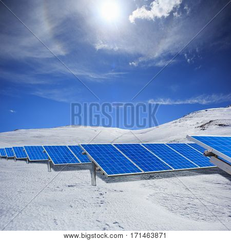 Modern Solar Station With Blue Panels Standing In Winter Field With White Snow And Hills At The Hori