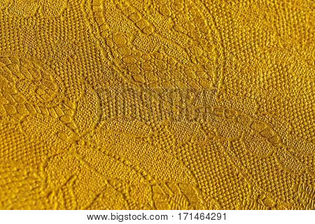 Genuine leather with an abstract ornament. Closeup on a leather texture, yellow color. For modern pattern, wallpaper or banner design. With place for your text