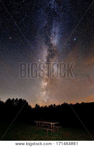 Milky Way over forest with barbeque bench in park in Stowe, Vermont.