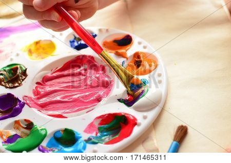 Child's hand holding a paintbrush dipping into a palette full of colorful paint