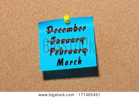 A conceptual image of spring beggining. Inscription March month and crossed out winter monthes December, January, February on blue sticker.