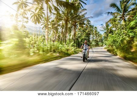 driving vintage motorbike fast through country side in Thailand shot with motion blur and lens flare