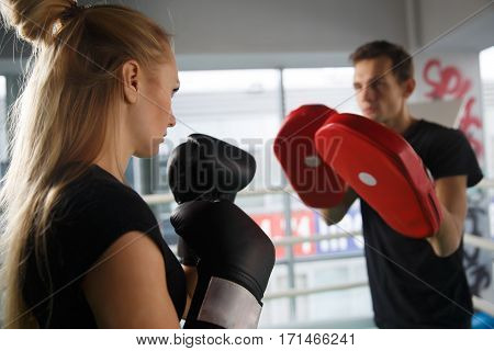 Young couple trains in boxing in gym
