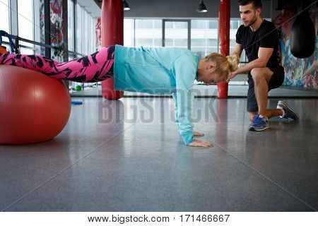 Young woman on fitball at gym in sportswear