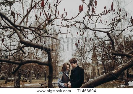 Romantic Stylish Couple Hugging Gently, Holding Hands In Autumn Park Under Unusual Tree. Man And Wom