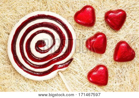 A retro looking photo of lollipop and heart shaped candies on a straw background.