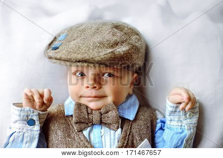 adorable newborn baby boy in brown waistcoat hat bow-tie and blue shirt smilling to the camera