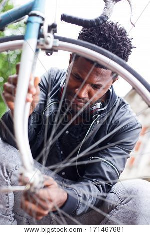 a young man checking his bike wheel