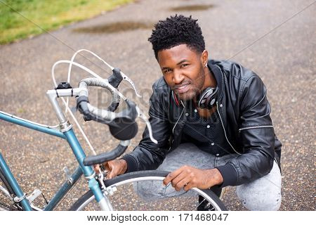 a young man checking his bicycle tires.