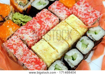 Appetizing sushi pieces with chopstickson white plate isolated top view closeup