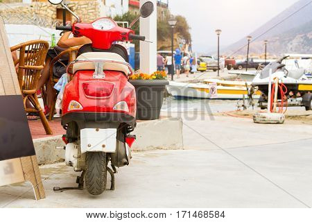Red two-wheeled moped parked on Mithos beach promenade in sea bay of resort village Bali. Classic Greek stone architecture of resort tourists walk streets of city. Rethymno Crete Greece