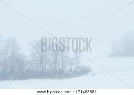 Foggy winter landscape. Top view of a frozen river and islands with trees. Fishermen on the ice. Dnipro river, Kiev, Ukraine