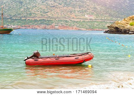 Empty motorboat drifting on waves near rocky shore. Sea view from cliff at foot of mountain and Bay separated by rocky stone ledges. Village Bali - vacation destination resort. Rethymno Crete Greece