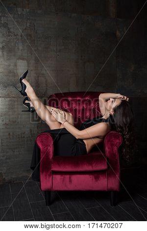 Cheeky Woman Lies In A Velvet Chair