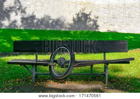 Wooden bench in the park. Motorcycle wheel stuck in the bench. Motorbike accident with a bench. Broken boards after accident.