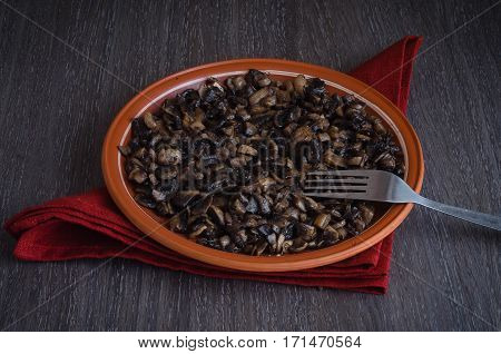 Roasted mushrooms on a plate, wooden background