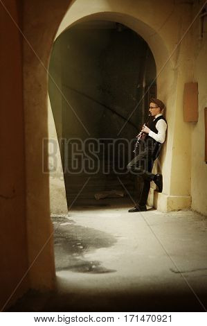 Stylish Hipster Man Playing Clarinet In Old Building Patio Under Arch On Background Of Old City