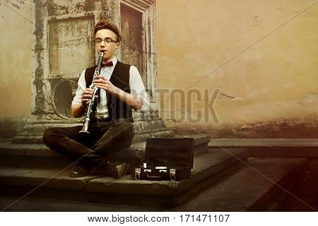 Stylish Hipster Man Playing Clarinet On Background Of Old City Street, Space For Text