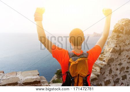 Brunet with hands raised amidst mountains against blue sky with clouds