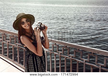 Happy Stylish Woman Hipster Holding Photo Camera And Smiling At Sunny Shore Near Water, Summer Trave