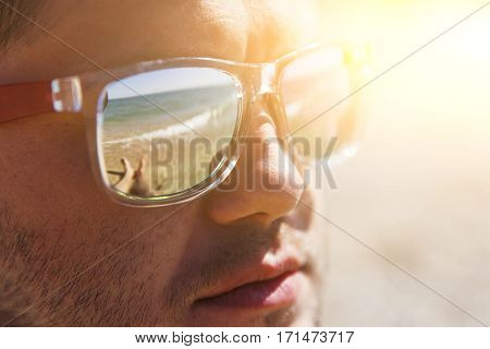 Man in sunglasses with reflective in their seashore