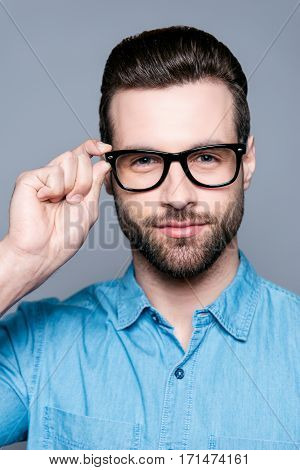 Portrait Of Handsome Young Serious Man Touching Glasses