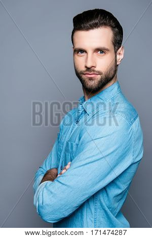 Portrait Of Serious Young Bearded Businessman With Crossed Hands