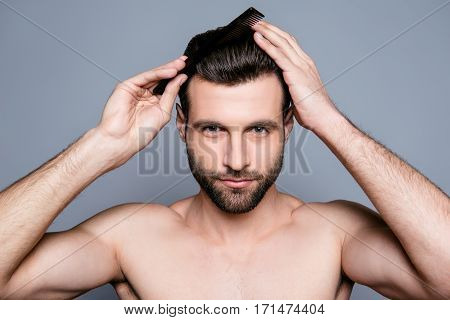 Portrait Of Handsome Young Guy Combing His Hair