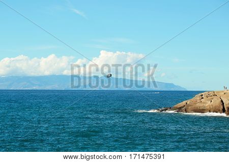 Parachute flies above beautiful blue sea water inshore along rocky coast outdoors on sunny summer day on sky background