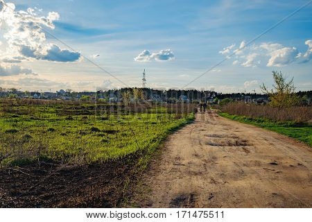 Rural spring landscape with dirt road through green fields and the village on the horizon, Irpin, Ukraine. View of typical Ukrainian rural landscape in spring.