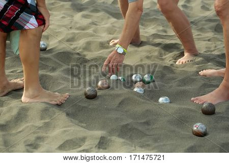 Legs and hands of people or men playing bocce sport with balls metal and plastic boules on natural sandy beach outdoors on summer day on grey sand textured background
