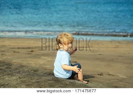 Cute Baby Boy Sits On Sand On Sandy Beach