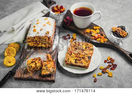 Homemade cake pie of dried fruits and nuts on the wooden board. Ingredients for cake pie dried fruits raisins figs prunes walnuts papaya pineapple cranberry. Drink tea in white cup.