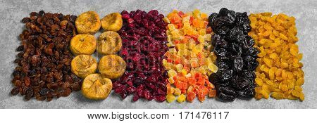 Assortment of dried fruit and candied fruit. Fruits figs prunes raisins papaya pineapple cranberries are laid out in rows on gray concrete background.