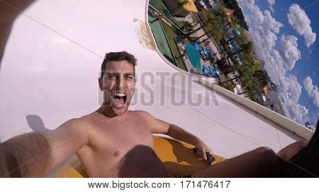 Man having fun and sliding down in a water slide