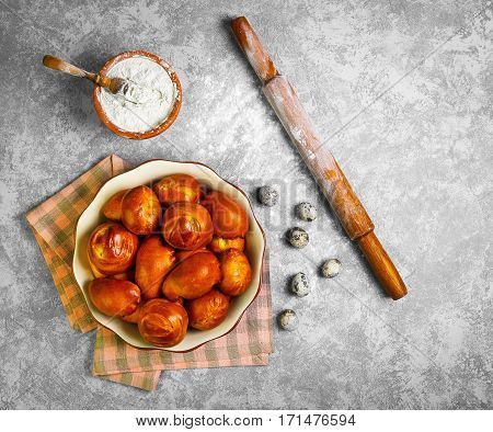 Preparing buns bread. Ingredients for cooking homemade buns bread wheat flour in bowl quail eggs wooden rolling pin. Fresh buns in a ceramic bowl on gray concrete background.