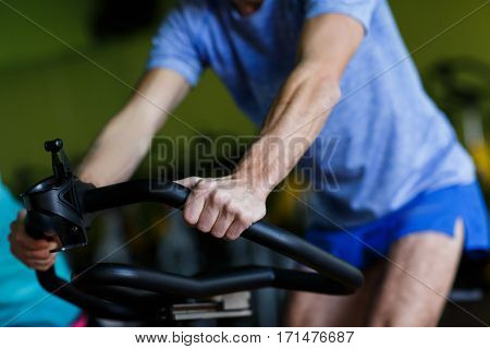 Sportsman engaged on stationary bike at sports center