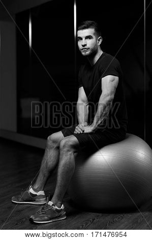 Young athlete sits on fitball at sports center, black and white photo