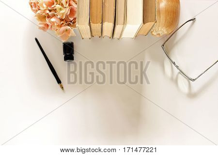 Top view of a charming desk top with vintage book stack, flowers, eyeglasses and pen and ink framing open white space.