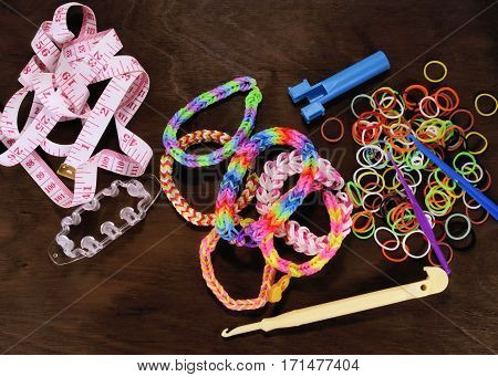 Wristbands and rings made of rubber bands (Rainbow loom Colored rubber bands for weaving) holding handful rubber bands