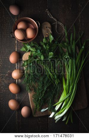 Chicken eggs with greens on the wooden table top view