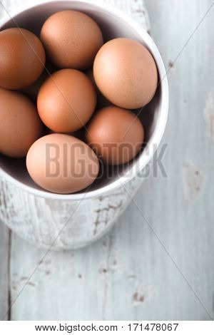 Chicken eggs in the ceramic bowl on the white wooden table top view