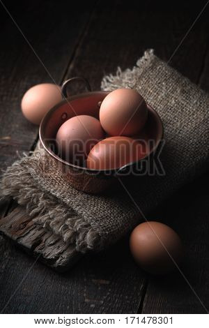 Eggs in the cooper pot on the wooden table vertical