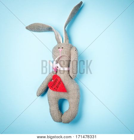 Easter. Easter bunny on a blue background. Rabbit. Easter ideas. Easter eggs. Space for text. Black lettering on a heart happy easter.
