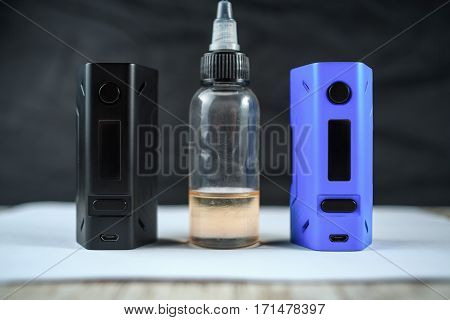 Electronic Cigarette Mod And A Jar With Fluid. Ends.